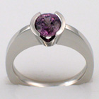 Platinum ring with v-cut semi-bezel-set round purple pastel sapphire on high-rise, flat-sided shank.