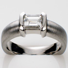 "Platinum ring with 1.06 ct. radiant-cut diamond in polished ""bracket-style"" semi-bezel on heavy-duty shank with brushed finish."