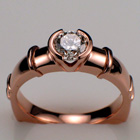 14 Karat Rose gold ring with 0.55 ct. round brilliant diamond in semi-bezel with decorative bars.