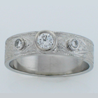 Hand-engraved platinum band with three round diamonds set in low-profile bezels.