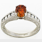 Hand-engraved platinum diamond ring with natural orange center and channel-set round sides.