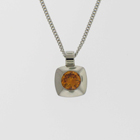 Platinum pendant with round orange diamond in square pillow bezel.
