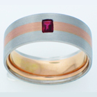 Brushed Platinum band with 14 karat rose gold inlay and flush-set emerald-cut ruby.
