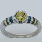 Platinum diamond ring with yellow center and blue green and yellow diamond channels.