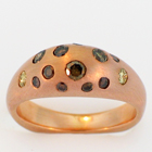 Brushed 14 karat rose gold ring with flush-set natural colored diamonds in gypsy-style shank.
