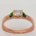 14 karat rose gold knife-edge saddle ring with a princess-cut diamond and two natural green colored diamond trilliants.
