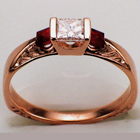 Hand-engraved 14 karat rose gold knife-edge saddle ring with a princess-cut diamond and two princess-cut rubies.