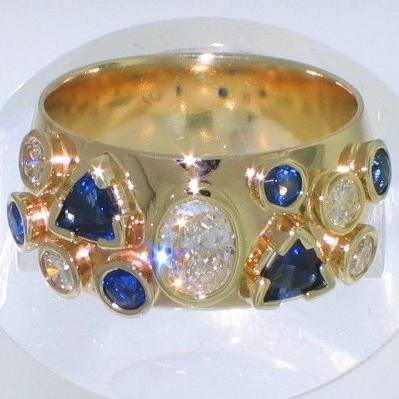 14 Karat Yellow Gold multi-bezels band with oval-shaped diamond center and diamonds and sapphires in various shapes and sizes set around band