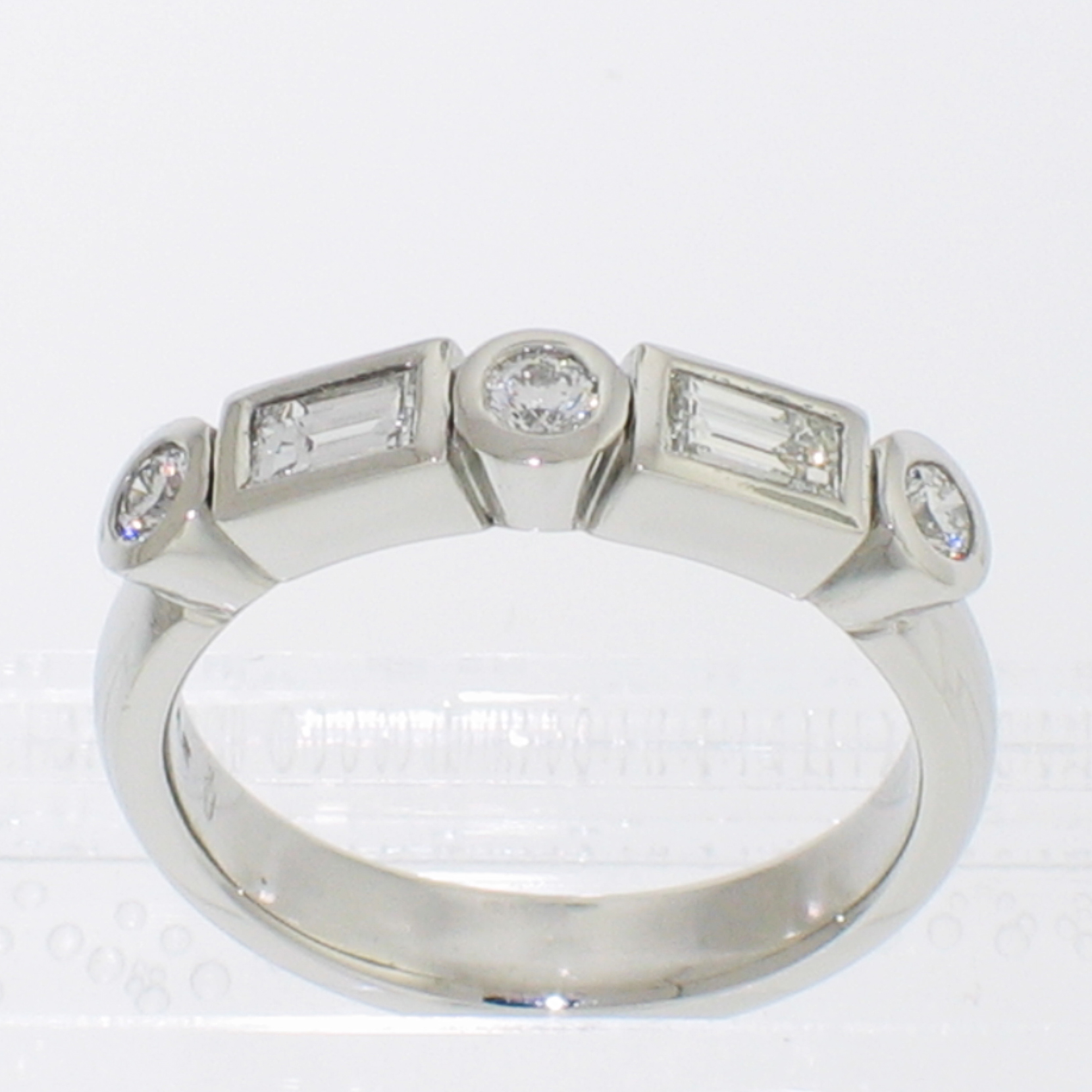 Platinum bezels band with alternating round brilliant and step-cut baguette diamonds