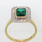 "18 Karat and Platinum ""halo"" ring with Emerald in full-bezel setting and bead-set diamonds on halo plate around emerald"