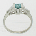 Platinum 3-stone ring with irradiated blue princess-cut diamond channel-set in angled saddle setting with tapered step-cut baguettes