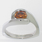 Platinum Asymmetrical wrap-around solitaire with channel-set oval-shaped natural orange-colored diamond