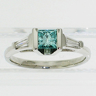 Platinum 3-stone ring with irradiated blue princess-cut diamond channel-set in angled saddle setting with tapered step-cut baguettes (alternate view)