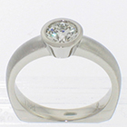 Palladium solitaire ring with 0.73ct round brilliant diamond in polished full bezel setting on matte-finished heavy round shank