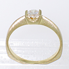 14 Karat yellow gold solitaire with round diamond in square saddle setting on pinched shank
