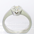 Platinum solitaire ring with round brilliant diamond set into v-cut semi-bezel setting on brushed shank