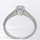 Platinum solitaire ring with 0.25 ct round brilliant diamond in full bezel setting on smooth shank