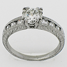 "Platinum hand-engraved diamond ring with 1 carat round brilliant diamond in fancy ""fishtail"" style setting on tapered channel shank"