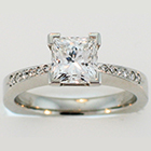 Platinum ring with Princess-cut diamond in 4-prong setting and bead-set melee round diamonds on pinched shank