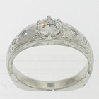 Platinum hand-engraved gypsy-style ring with 0.48 carat round brilliant diamond in low-profile six-prong setting with round melee diamonds flush-set into shank