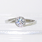 Platinum low-profile wrap-around bezel ring with 0.51 carat round-brilliant diamond set in low bezel