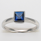 Platinum solitaire with princess-cut blue sapphire in bezel setting