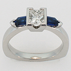 Platinum diamond ring with step-cut tapered bullet-shaped blue sapphire sides.