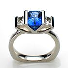 Platinum ring with emerald-cut blue sapphire and trapedoid-shaped side diamonds in w-shaped saddle setting.