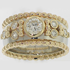 Platinum half-round tapered band with 18 Karat Yellow Gold beaded borders and bezel-set round diamonds with bead accents