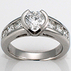 platinum ring with round brilliant diamond in semi bezel on tapered-channel shank.