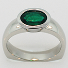 Palladium ring with oval-shaped emerald in bezel setting.
