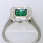 "Platinum ""halo"" ring with square Emerald in full bezel and bead-set diamonds on halo plate around emerald"