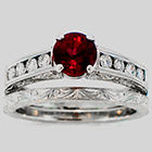 Hand-engraved Platinum wedding set with 1.23 carat round Ruby in 4-prong setting with 0.40carats total weight of round diamonds channel-set in sides and matching hand-engraved platinum band.