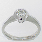 Palladium solitaire ring with round brilliant diamond in full bezel with angled rim