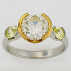 Platinum ring with 2 carat round brilliant yellow diamond in 18 karat yellow gold bezel with fancy intense yellow pear-shaped diamonds on the sides.
