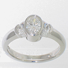 Platinum diamond ring with oval center and crescent moon-shaped sides.