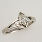 platinum split-shank ring with semi-bezel-set marquis-cut diamond and tapered channel of side stones