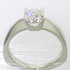Platinum solitaire ring with round brilliant diamond channel-set into square saddle setting