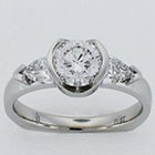 Platinum diamond ring with round brilliant in semi-bezel and crescent shield-cut diamonds on sides.