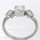 Platinum 3-stone ring with princess-cut diamonds set in full bezels on knife-edge band