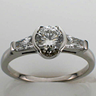 platinum ring with 0.74 carat round brilliant center diamond in semi-bezel and 0.38 carat total weight(0.19 ct. each) tapered brilliant baguettes.