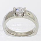 Platinum solitaire with 0.72 carat round brilliant diamond channel-set into low-profile saddle setting