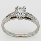 Platinum hand-engaved diamond ring with empire-style setting on gallery-style shank.