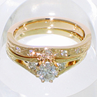 14 Karat Yellow gold split-shank hand-engraved wedding set with flush-set round melee diamonds in hand-engraved band