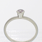 Platinum stacker ring with 0.18 carat round brilliant diamond in full high-profile polished bezel on brushed half-round band