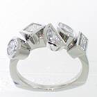 Platinum ring with assorted shapes and sizes of bezel-set diamonds.