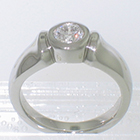 Platinum solitaire with 0.51 carat round brilliant diamond in full-bezel on thick shank with shoulders