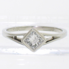 Platinum split-shank solitaire with diagonally-oriented bezel-set princess-cut diamond
