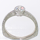 Platinum hand-engraved solitaire with 0.54 carat round brilliant diamond in full bezel