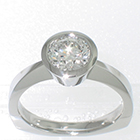 Palladium solitaire with 1 carat round brilliant diamond in full tapered bezel setting on pinched shank with corners